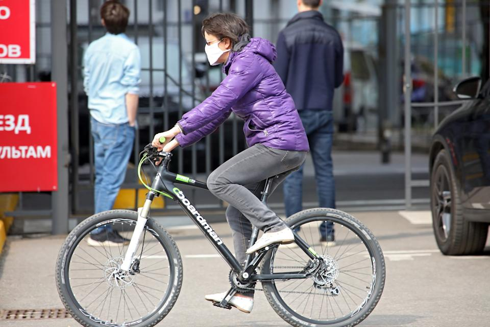 KHARKIV, UKRAINE - APRIL 14, 2020 - A woman in a face mask rides a bicycle on a street during lockdown caused by the coronavirus pandemic, Kharkiv, northeastern Ukraine. - PHOTOGRAPH BY Ukrinform / Barcroft Studios / Future Publishing (Photo credit should read Vyacheslav Madiyevskyy/ Ukrinform/Barcroft Media via Getty Images)