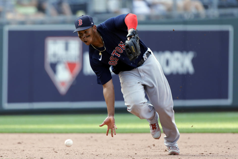 Boston Red Sox third baseman Rafael Devers attempts to bare-hand a ground ball hit by Kansas City Royals' Kelvin Gutierrez during the ninth inning of a baseball game at Kauffman Stadium in Kansas City, Mo., Saturday, June 19, 2021. Gutierrez singled on the play. (AP Photo/Colin E. Braley)