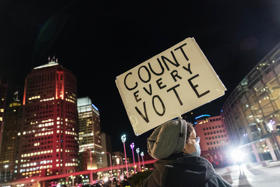 """FILE - In this Nov. 4, 2020, file photo, Betsy Camardo, who supports Joe Biden, holds a sign outside the central counting board where ballots in the general election are counted in the city at the TCF Center in Detroit. President Donald Trump and his allies have fomented the idea of a """"rigged election"""" for months, promoting falsehoods through various media and even lawsuits about fraudulent votes and dead voters casting ballots. While the details of these spurious allegations may fade over time, the scar it leaves on American democracy could take years to heal. (AP Photo/David Goldman, File)"""