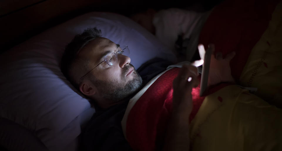 A man using his mobile phone in bed