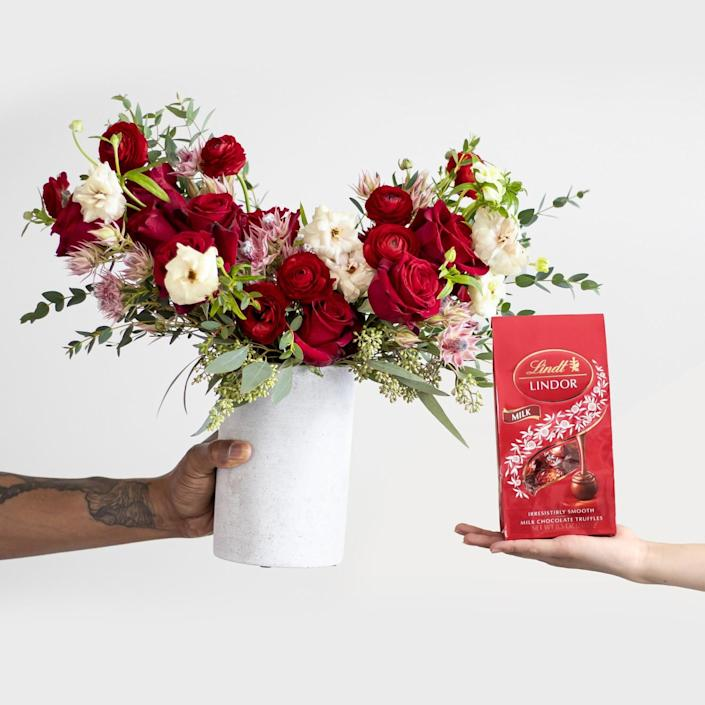 A photo of hands holding Farmgirl Flowers and Lindt Chocolates.