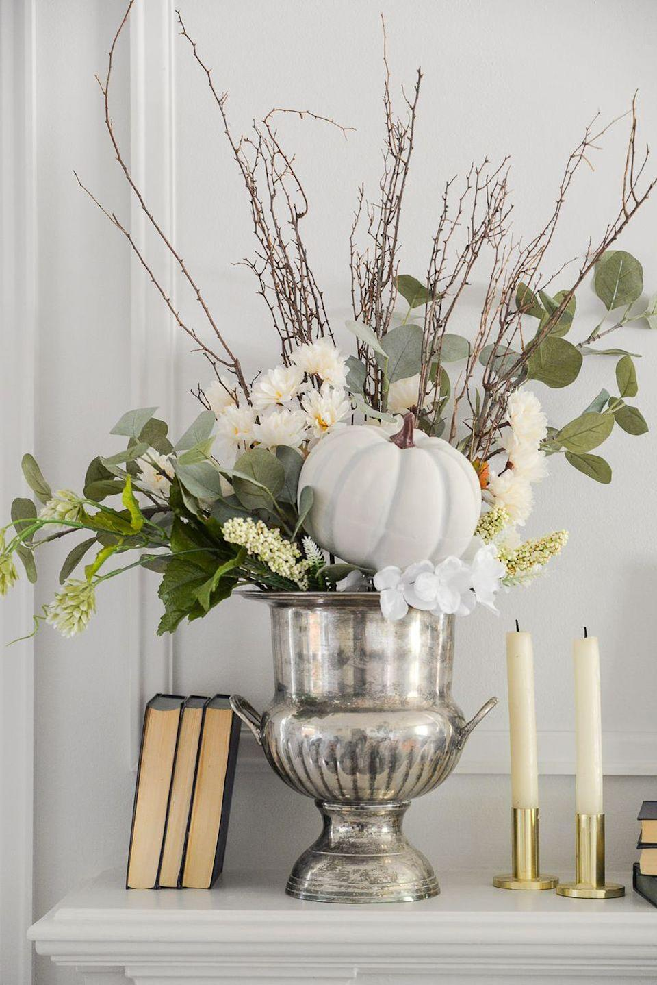 """<p>To make a fall-ish floral arrangement for your mantel, start with a silver wine bucket and layer it with faux florals, branches, and a pumpkin.</p><p><strong>Get the tutorial at <a href=""""https://www.ramblingrenovators.ca/2020/09/fall-flower-arrangement-diy.html"""" rel=""""nofollow noopener"""" target=""""_blank"""" data-ylk=""""slk:Rambling Renovators"""" class=""""link rapid-noclick-resp"""">Rambling Renovators</a>.</strong></p><p><a class=""""link rapid-noclick-resp"""" href=""""https://go.redirectingat.com?id=74968X1596630&url=https%3A%2F%2Fwww.walmart.com%2Fip%2FSilver-Plated-Brass-Wine-Bucket%2F337375177&sref=https%3A%2F%2Fwww.thepioneerwoman.com%2Fhome-lifestyle%2Fcrafts-diy%2Fg36891743%2Ffall-mantel-decorations%2F"""" rel=""""nofollow noopener"""" target=""""_blank"""" data-ylk=""""slk:SHOP WINE BUCKETS"""">SHOP WINE BUCKETS</a></p>"""