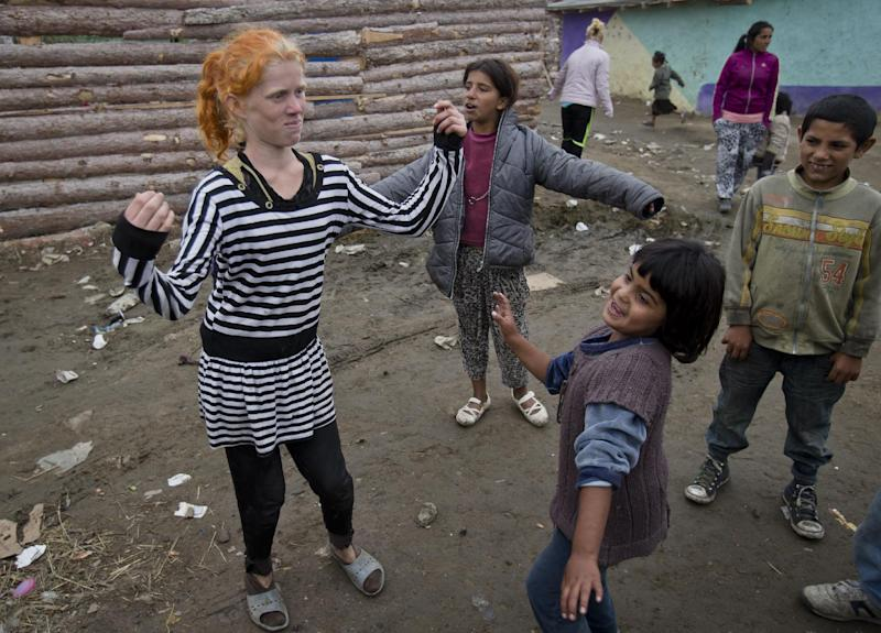 "Minka Ruseva, daughter of Sasha Ruseva, left, dances along with other children in a Roma neighborhood of Nikolaevo, Bulgaria, Friday, Oct. 25, 2013. Sasha Ruseva, a Bulgarian Roma woman from this town, is under investigation by Bulgarian authorities trying to find out if she is the mother of a suspected abduction victim in neighboring Greece known as ""Maria"" whose case has triggered a global search for her real parents. (AP Photo/Vadim Ghirda)"