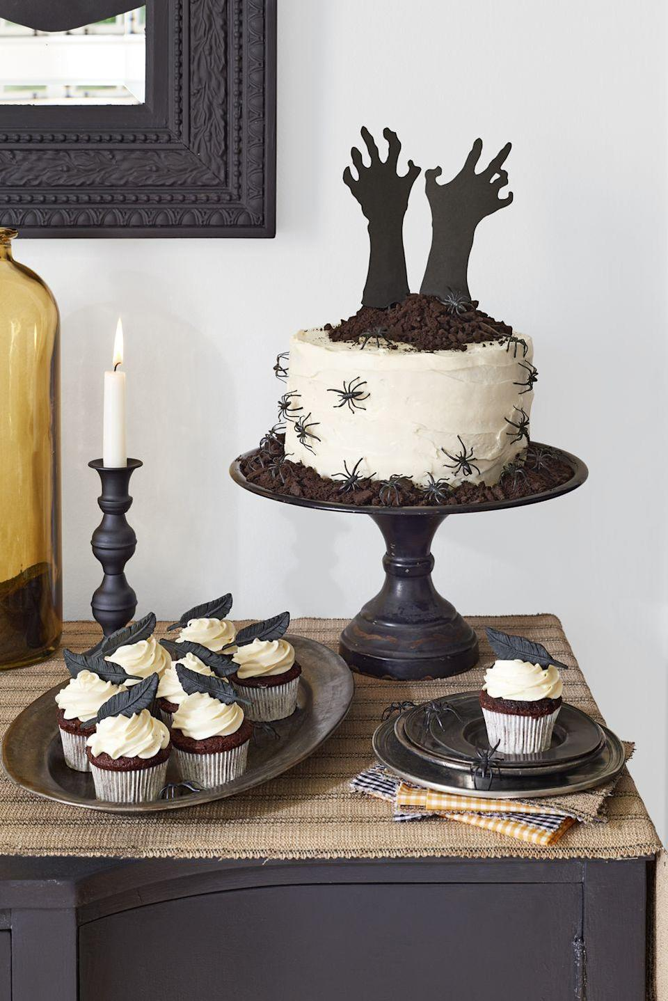 """<p>The eye-catching """"Help Me!"""" cake is simply a store-bought white cake with a few dark twists. (Talk about hands-off!) </p><p>Start with a store-bought frosted layer cake. Cut out a pair of arms and hands in black craft paper and tape to skewers to help them stand upright. Pile on a mound of """"dirt""""— crumbled chocolate cookies—to give it that """"buried alive"""" vibe. Top vanilla-frosted cupcakes with <span class=""""redactor-unlink"""">edible fondant raven feathers</span>. For an extra hair-raising element, add plastic critters around the cake. </p><p><strong><a href=""""https://www.countryliving.com/food-drinks/recipes/a1568/circus-tent-frosting-3678/"""" rel=""""nofollow noopener"""" target=""""_blank"""" data-ylk=""""slk:Get recipe for buttercream"""" class=""""link rapid-noclick-resp"""">Get recipe for buttercream</a>.</strong></p>"""