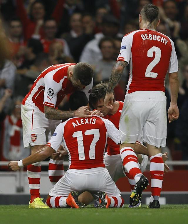 Arsenal's Alexis Sanchez, number 17, celebrates with teammates after scoring a goal during a second leg Champions League qualifying soccer match between Arsenal and Besiktas at Emirates Stadium in London Wednesday, Aug. 27, 2014.(AP Photo/Kirsty Wigglesworth)
