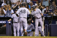 New York Yankees' Tyler Wade, right, greets Anthony Rizzo (48) after Rizzo scored on a single hit by Rougned Odor during the second inning of a baseball game, Saturday, July 31, 2021, in Miami. (AP Photo/Lynne Sladky)