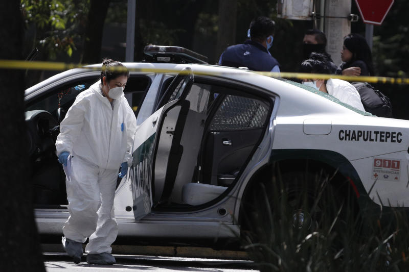 A forensic investigator inspects a police vehicle at the scene where the Mexican capital's police chief was attacked by gunmen in Mexico City, Friday, June 26, 2020. Heavily armed gunmen attacked and wounded Omar García Harfuch in an operation that left several dead. (AP Photo/Rebecca Blackwell)