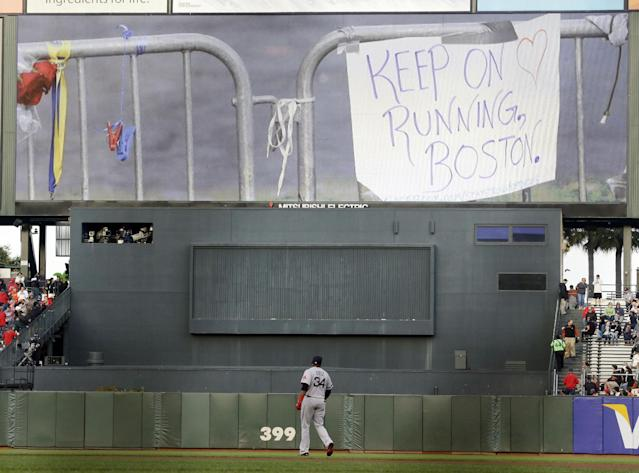 Boston Red Sox's David Ortiz warms up as images from the Boston marathon explosion flash on the screen during a ceremony honoring victims of the bombing before a baseball game against the San Francisco Giants on Monday, Aug. 19, 2013, in San Francisco. (AP Photo/Marcio Jose Sanchez)