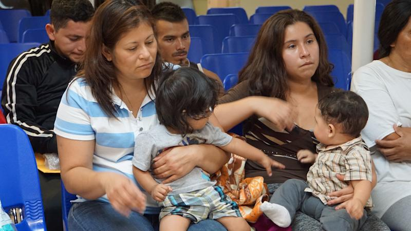 Mothers and children wait to be assisted by volunteers in a humanitarian center in the border town of McAllen, Texas, on June 14, 2018.