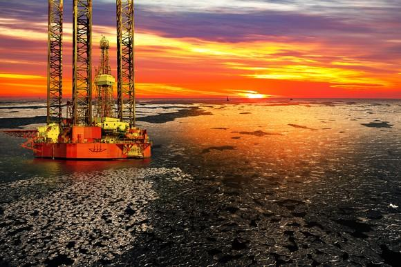 An offshore drilling rig at sunrise over a frozen sea.