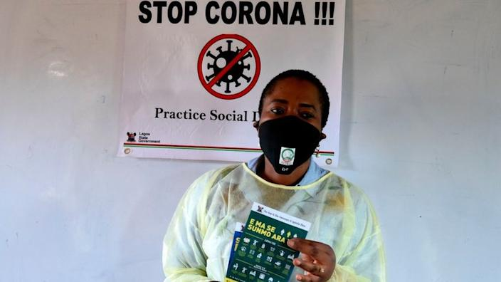 A person holding a pamphlet in Nigeria that tells people how to contain the spread of the virus