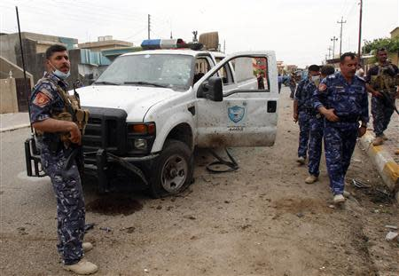 Iraqi security forces inspect the site of a suicide bombing outside a polling station in Kirkuk