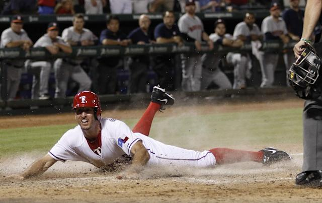 Texas Rangers' Adam Rosales slides with the game-winning run on a sacrifice fly hit Elvis Andrus against the Houston Astros during the ninth inning of a baseball game, Wednesday, Aug. 21, 2013, in Arlington, Texas. The Rangers won 5-4. (AP Photo/Jim Cowsert)