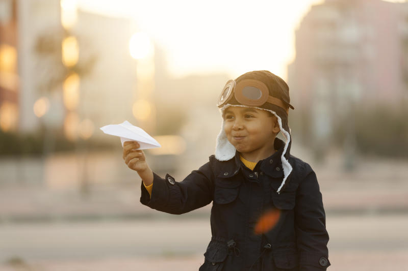Small boy playing with paper plane