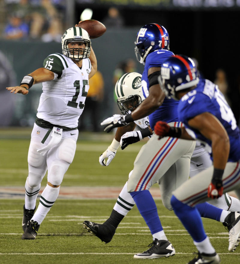 New York Jets quarterback Tim Tebow,left, looks to throw past New York Giants defenders during the second half of a preseason NFL football, Saturday, Aug. 18, 2012, in East Rutherford, N.J. (AP Photo/Bill Kostroun)