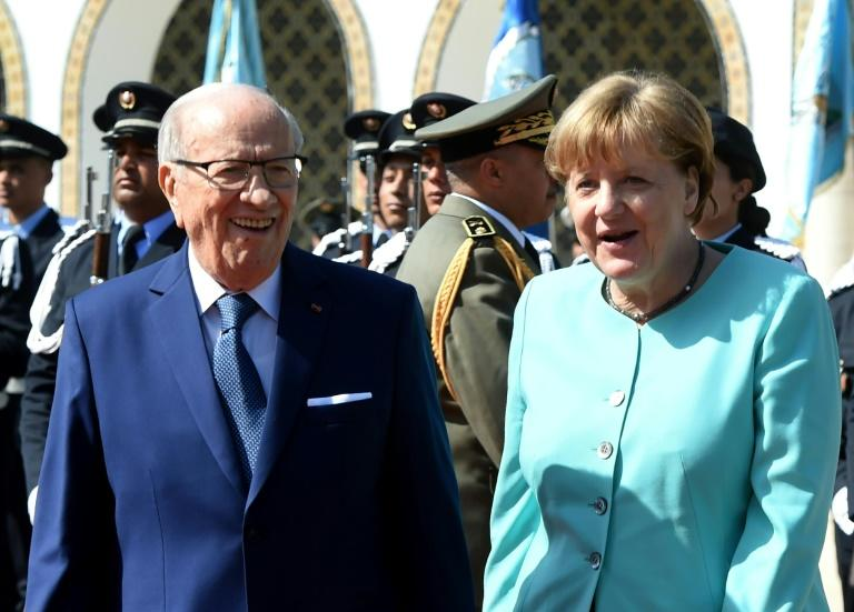 Tunisian President Beji Caid Essebsi and German Chancellor Angela Merkel review a guard of honour in Tunis, on March 3, 2017
