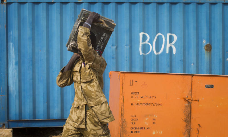 A South Sudanese government soldier carries an ammunition box from storage at the airport in Bor, Jonglei State, South Sudan Sunday, Jan. 19, 2014. Leaders for warring sides in South Sudan's monthlong internal conflict say they are close to signing a cease-fire and the South Sudanese military spokesman said that army forces had retaken the key city of Bor Saturday, defeating 15,000 rebels. (AP Photo/Mackenzie Knowles-Coursin)