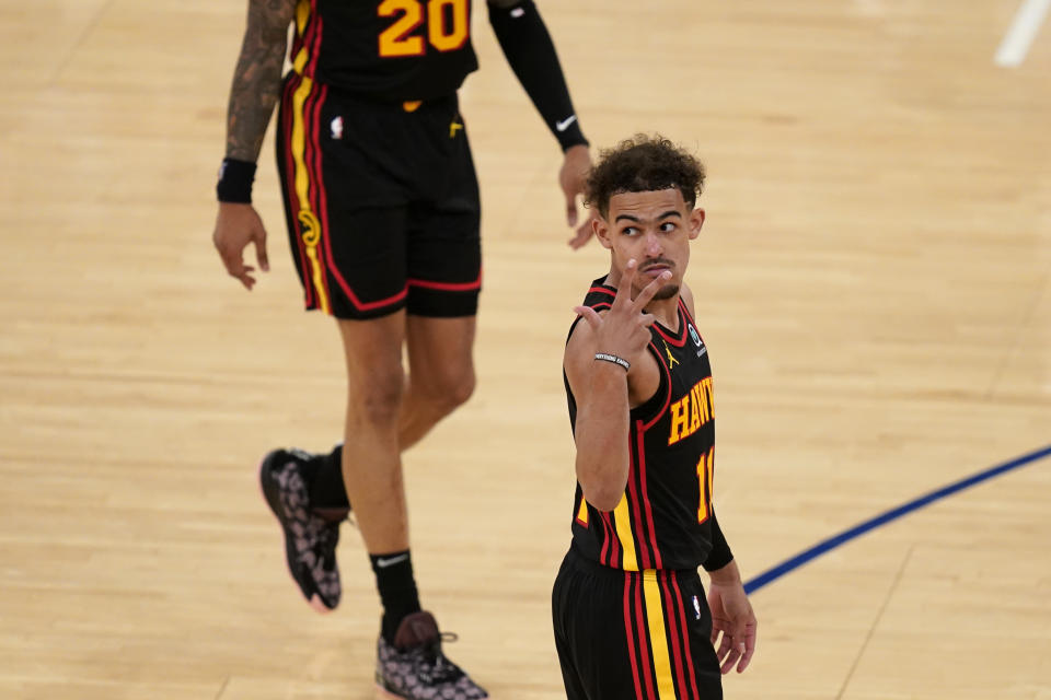 Trae Young gestures with three fingers.
