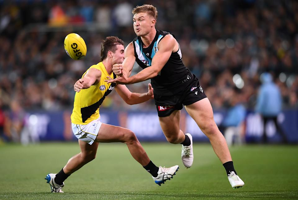 Ollie Wines (pictured right) handballs to a teammate during the round four AFL match between the Port Adelaide Power and the Richmond Tigers.