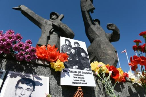 Historic photographs of soldiers and flowers are placed in front of the Victory Monument in Riga