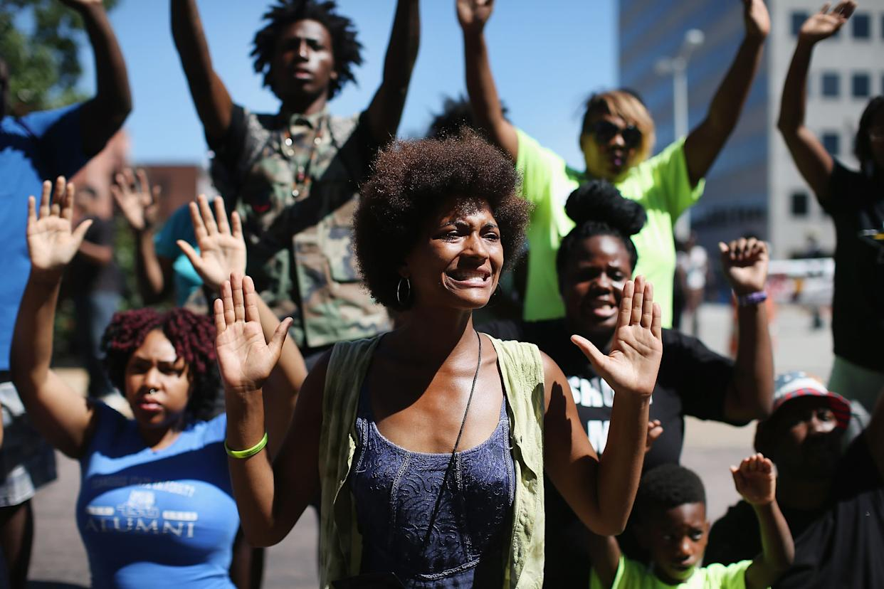 CLAYTON, MO - AUGUST 12: Demonstrators raise their hands and chant 'hands up, don't shoot' during a protest over the killing of Michael Brown on August 12, 2014 in Clayton, Missouri. Some reports state that Brown hand his hands in the air when he was shot and killed by a police officer on Saturday in suburban Ferguson, Missouri. Two days of unrest including rioting and looting have followed the shooting in Ferguson. Browns parents have publicly asked for order. (Photo by Scott Olson/Getty Images)