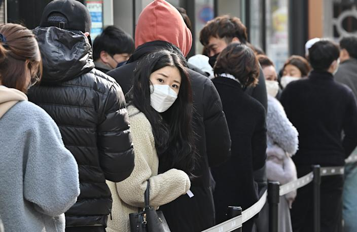 People wait in line to buy face masks in front of a store at Dongseongro shopping district in Daegu on February 27, 2020.
