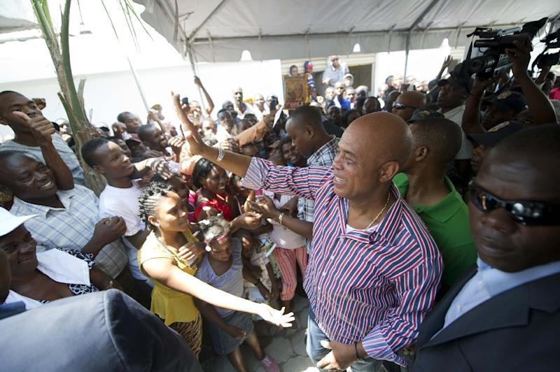 Haitian President Michel Martelly (C) is greeted by supporters while attending the inauguration of neighborhood of Morne Lazarre, in the commune of Petion Ville, Port-au-Prince, on April 17, 2015 (AFP Photo/Hector Retamal)