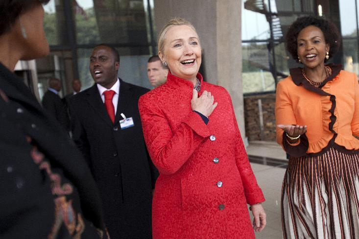 FILE - In this Aug. 7, 2012 file photo, Secretary of State Hillary Rodham Clinton, left, and South Africa's Foreign Minister Maite Nkoana-Mashabane, react with delight during a rare snow flurry as they leave business meetings in Pretoria, South Africa. On an epic safari through Africa, U.S. Secretary of State Hillary Rodham Clinton braved Uganda's Ebola outbreak, dealt with a swarm of angry Malawian bees, endured a rare South African snowstorm and shimmied on a dance floor in South Africa, earning the nickname the Secretary of Shake. And as she wrapped up her nine-nation African tour on Friday in Benin,Clinton shattered her own already herculean travel record. (AP Photo/Jacquelyn Martin, File, Pool)