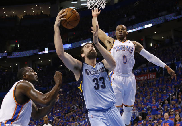 Memphis Grizzlies center Marc Gasol (33) shoots between Oklahoma City Thunder center Kendrick Perkins (5) and guard Russell Westbrook (0) in the first quarter of Game 7 of an opening-round NBA basketball playoff series in Oklahoma City, Saturday, May 3, 2014. (AP Photo/Sue Ogrocki)