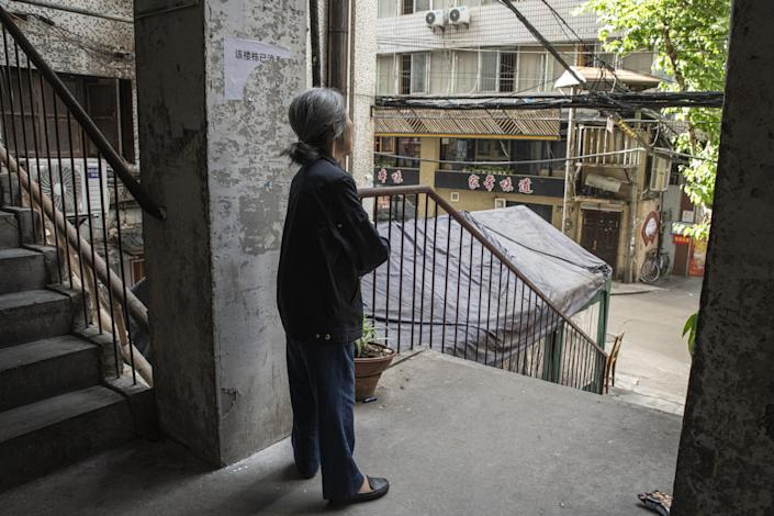 "A woman in Wuhan stands just outside her apartment in May 2020. Residents feared new limits on movement. <span class=""copyright"">(For The Times)</span>"