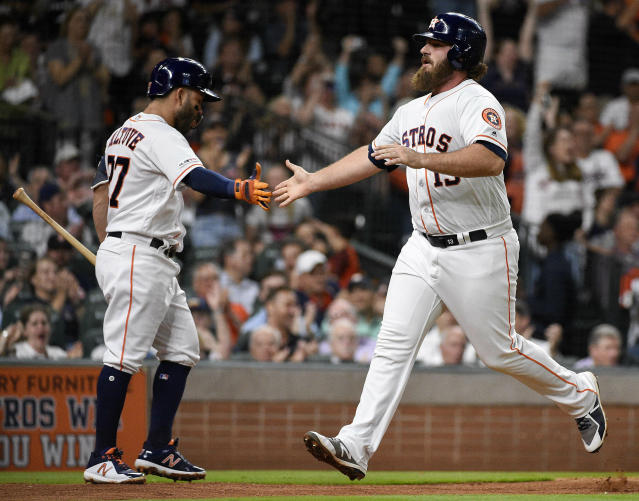 Houston Astros' Tyler White, right, celebrates his run scored on George Springer's RBI single with Jose Altuve during the third inning of a baseball game against the Minnesota Twins, Tuesday, April 23, 2019, in Houston. (AP Photo/Eric Christian Smith)