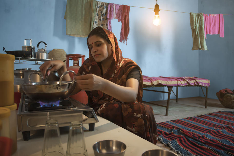 Indian Woman Sitting In Kitchen Cooking Food