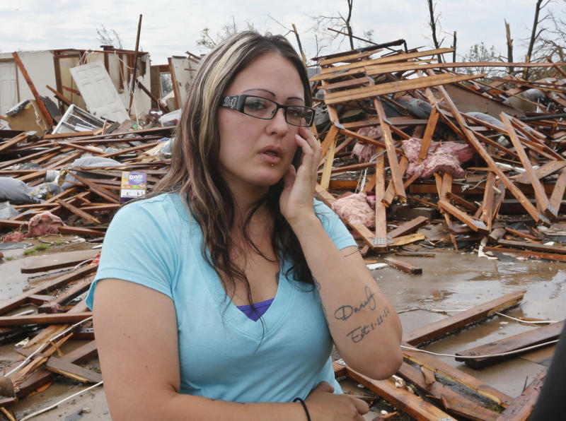 LaTisha Garcia wipes a tear from her eye in front of her demolished home as she talks about carrying her injured daughter following Monday's tornado in Moore, Okla., Thursday, May 23, 2013. (AP Photo/Sue Ogrocki)