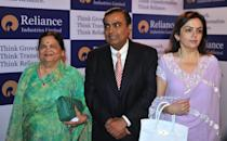 Chairman of India's Reliance Industries (RIL) Mukesh Ambani (C) poses with his wife Nita (R) and mother Kokilaben (L) after arriving for the company's 36th annual general share holders meeting in Mumbai on June 18, 2010. India's richest man Mukesh Ambani addressing company shareholders at the annual general meeting of his flagship company RIL said that the legal disputes with his younger brother Anil Ambani with whom he had a long and bitter feud was a thing of the past and indicated towards a truce. The Ambanis, who were at loggerheads since their family empire was split in 2005, made up last month, bringing an end to their acrimonious and highly public feud. Last month, the two Reliance groups agreed to scrap the contentious business pact signed in 2006, which had fuelled the acrimonious row between the brothers, giving them freedom to operate in several sectors. AFP PHOTO/ Punit PARANJPE