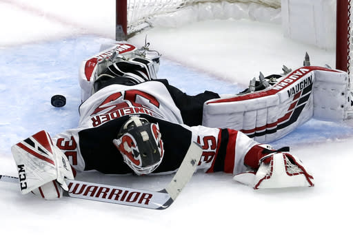 New Jersey Devils goalie Cory Schneider cannot stop a goal by Chicago Blackhawks center Jonathan Toews during the second period of an NHL hockey game Thursday, Feb. 14, 2019, in Chicago. (AP Photo/Nam Y. Huh)