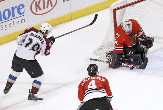 Chicago Blackhawks goalie Corey Crawford (50) makes a save on a shot by Colorado Avalanche center Nathan MacKinnon (29) as Niklas Hjalmarsson (4) watches during the second period of an NHL hockey game Tuesday, March 4, 2014, in Chicago. (AP Photo/Charles Rex Arbogast)