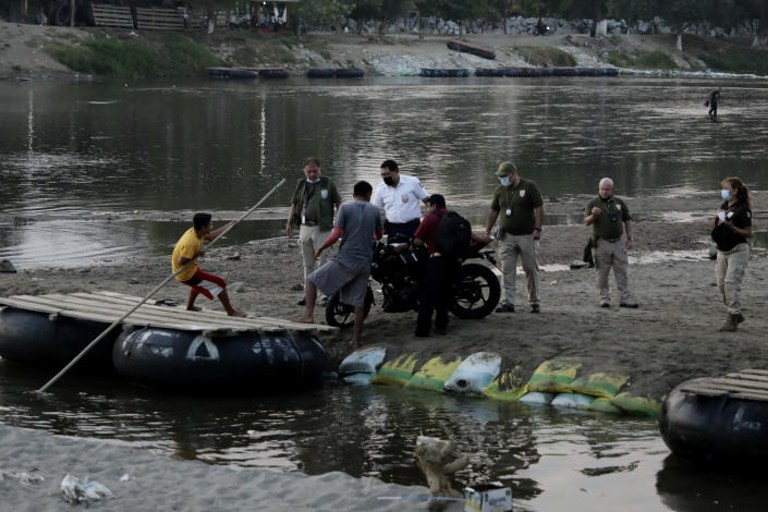 Mexican immigration agents review the IDs of Guatemalan merchants at an access point to the Suchiate River, the natural border between Guatemala and Mexico, near Ciudad Hidalgo, Mexico, Sunday, March 21, 2021. Mexico sent hundreds of immigration agents, police and National Guard to its southern border to launch an operation to crack down on migrant smuggling. (AP Photo/Eduardo Verdugo)
