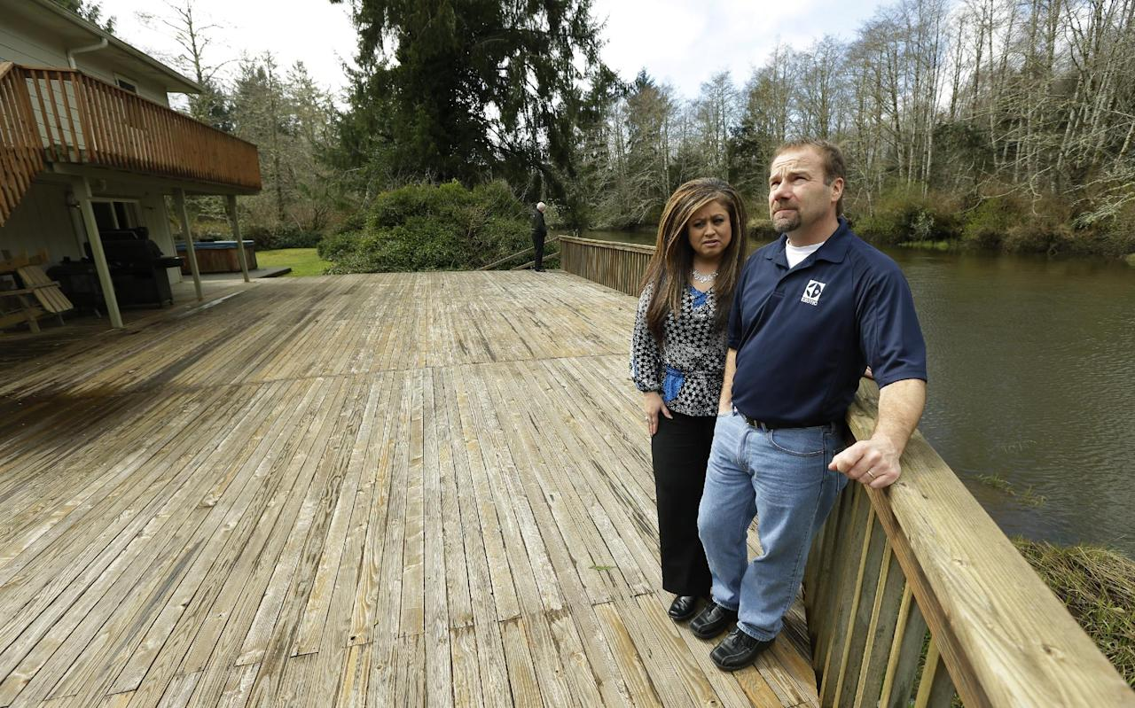 Darrin Moir, right, and his wife Leonor Moir, stand Monday, March 18, 2014 on the deck of their house, which is located along the Little Hoquiam River in Hoquiam, Wash. The Moirs currently pay about $1,700 annually for flood insurance, even though they say they have never had a major flooding incident since buying their home in 1996. Possible rate increases could up their premiums to more than $9,000 a year, which they say could prevent them from eventually selling their home. (AP Photo/Ted S. Warren)