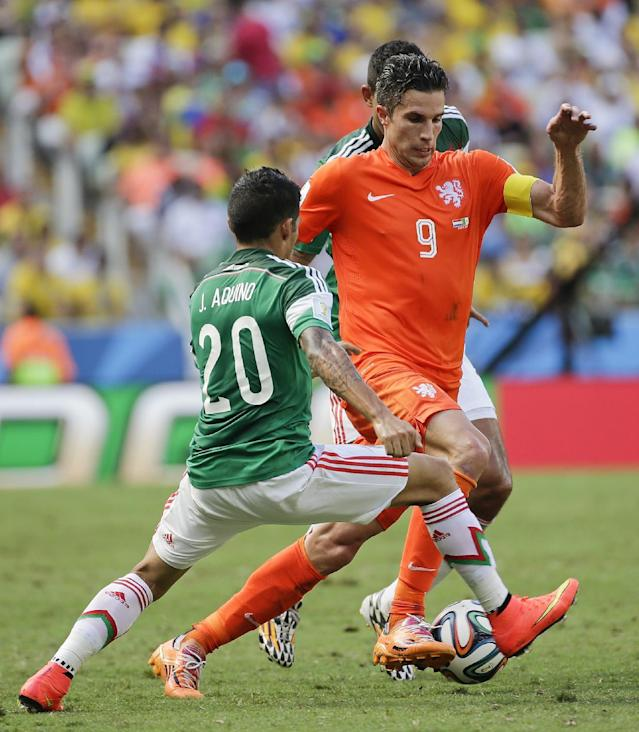 Mexico's Javier Aquino tries to stop an attack by Netherlands' Robin van Persie during the World Cup round of 16 soccer match between the Netherlands and Mexico at the Arena Castelao in Fortaleza, Brazil, Sunday, June 29, 2014. (AP Photo/Felipe Dana)