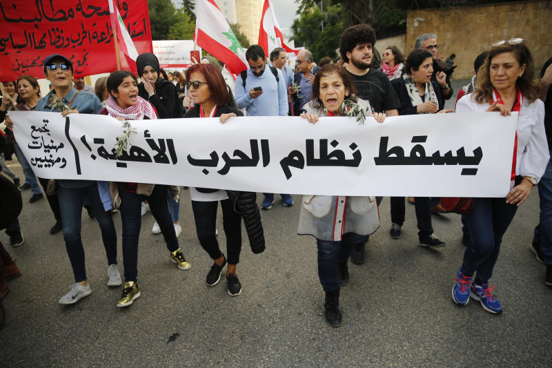"Lebanese protesters carry an Arabic banner that reads, ""Down with the civil war regime,"" as they march in Beirut, Lebanon, Sunday, Dec. 1, 2019. Protesters have been holding demonstrations since Oct. 17 demanding an end to widespread corruption and mismanagement by the political class that has ruled the country for three decades. (AP Photo/Hussein Malla)"