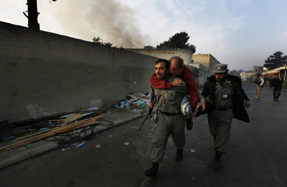 An Afghan police officer carries an injured unidentified German national as smoke bellows from the site of an attack in Kabul, Afghanistan on Wednesday, Oct. 28, 2009. Gunmen attacked a guest house used by U.N. staff in the Afghan capital of Kabul. (AP Photo/Gemunu Amarasinghe)