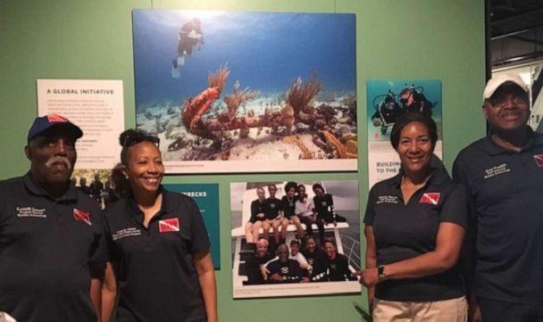 PHOTO: From left, DWP divers Ken Stewart, Angela Jones, Melody Garrett and Ernie Franklin with their picture in the National Museum of African American History and Culture. (Melody Garrett)
