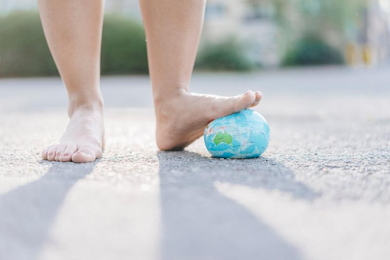 Foot of young woman stepping on globe. Source: Getty Images