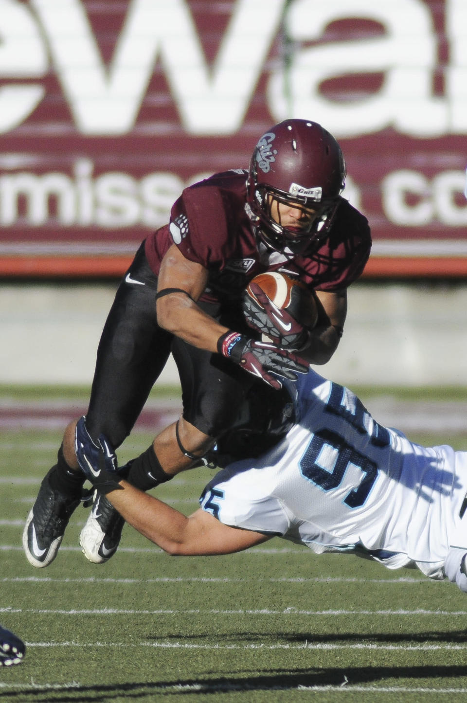 Montana running back Jordan Canada, top, is tripped by San Diego defensive lineman Jonathan Petersen (95) during the first half of an NCAA college football playoff game, Saturday, Nov. 29, 2014, in Missoula, Mont. (AP Photo/Lido Vizzutti)