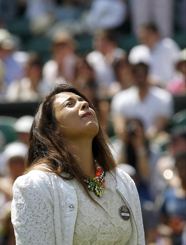 2013 Wimbledon champion Marion Bartoli of France looks up as she takes part in the coin toss for the match between Julia Glushko of Israel and Sabine Lisicki of Germany at the All England Lawn Tennis Championships in Wimbledon, London, Tuesday, June 24, 2014. Traditionally the reigning champion would play her first match on Centre Court but due to Bartoli's retirement the runner up Lisicki will open play. (AP Photo/Sang Tan)