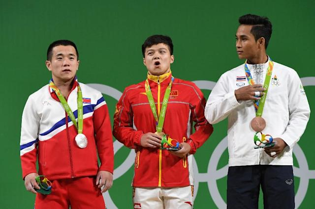 China's gold medallist Long Qingquan (C), North Korea's silver medallist Om Yun Chol (L) and Thailand's bronze medalist Sinphet Kruaithong pose with their medals after the men's 56kg weightlifting event at the Rio 2016 Olympic games, on August 7 (AFP Photo/Goh Chai Hin)