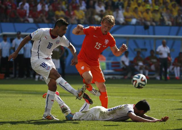 Chile's Gonzalo Jara fights for the ball with Dirk Kuyt of the Netherlands (C) beside his teammate Jean Beausejour (R) during their 2014 World Cup Group B soccer match at the Corinthians arena in Sao Paulo June 23, 2014. REUTERS/Sergio Moraes (BRAZIL - Tags: SOCCER SPORT WORLD CUP)