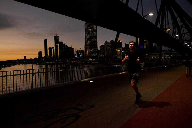 A man is seen jogging across the Goodwill Bridge as the sun sets in Brisbane.