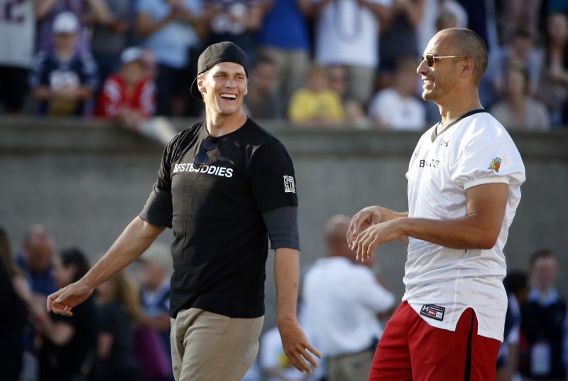 Former New England Patriots quarterback Tom Brady, left, walks with former teammate Christian Fauria during a charity football game in 2018. (AP Photo/Michael Dwyer, File)