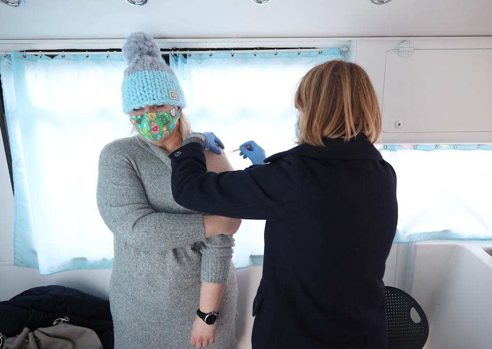 An NHS nurse gives Agata Skorynko, aged 41, a Covid-19 vaccination on board a modified bus, in the car park of the University of Greenwich, London. Picture date: Saturday February 13, 2021. (Photo by Yui Mok/PA Images via Getty Images)